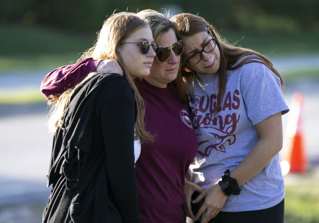 Marjory Stoneman Douglas High student Sophia Rothenberg, right, embraces her mother, Cheryl Rothenberg, and sister Emma Rothenberg at a memorial Thursday marking one year since the mass shooting at the school in Parkland, Florida.