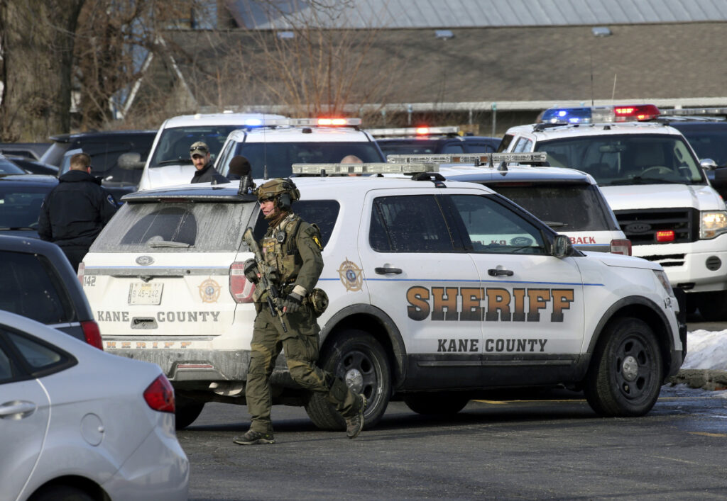 Law enforcement personnel gather near the scene where five people were shot to death in Aurora, Illinois, on Friday.