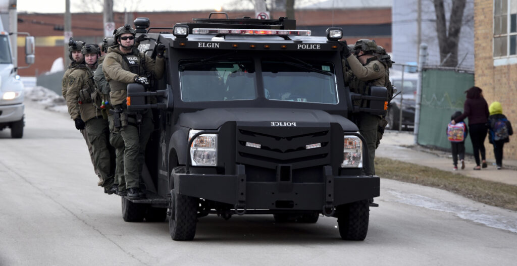 Police officers ride on a vehicle Friday near the site of a shooting at a manufacturing plant in Aurora, Ill.