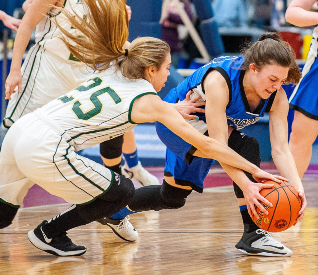 Rangeley's Olivia Pye, left, and Seacoast Christian's Katie Pilkington dive for a loose ball Saturday morning during a Class D South quarterfinal at the Augusta Civic Center. Rangeley won, 56-23.