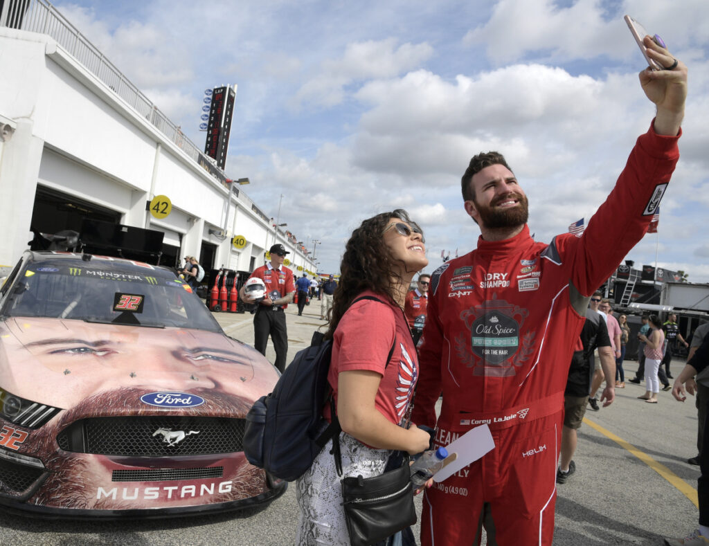 Corey LaJoie, right, poses for a selfie with Jenny Schnell in front of his car during a practice session Saturday for the Daytona 500. Lajoie, one of the eight Daytona rookies, has his face painted on the hood of his car.