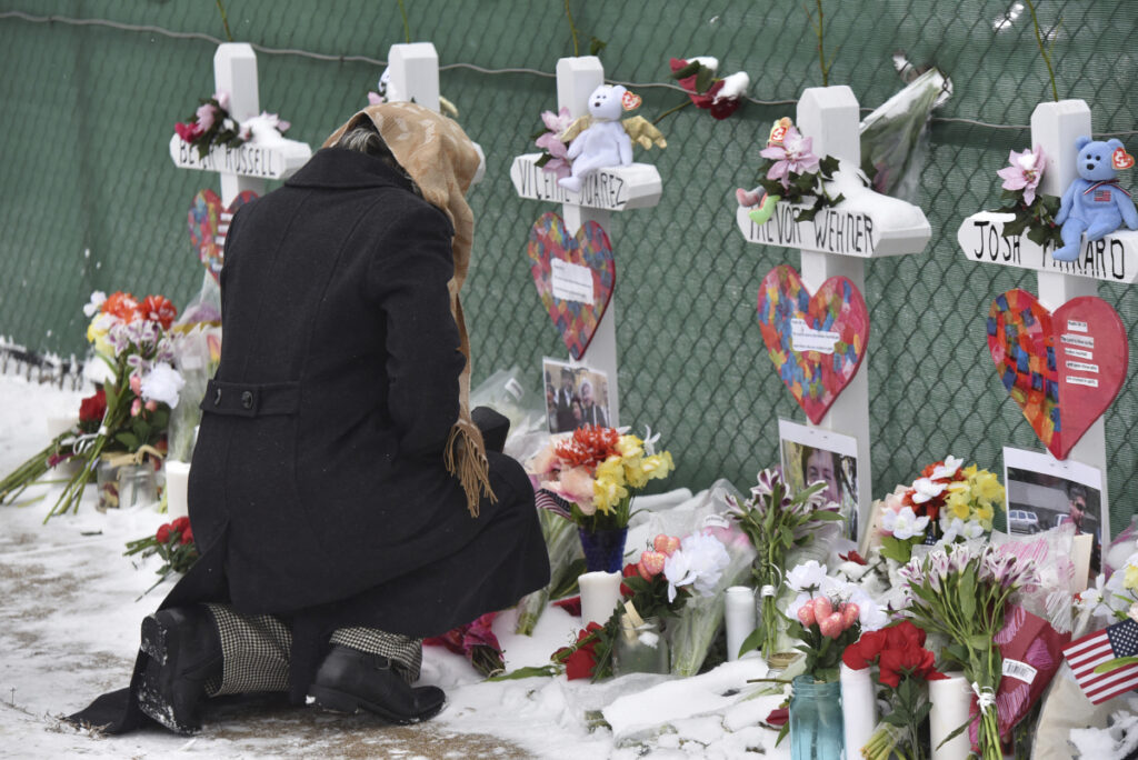 Mourners place flowers at the crosses outside of the Henry Pratt Co. in Aurora, Ill., on Sunday.