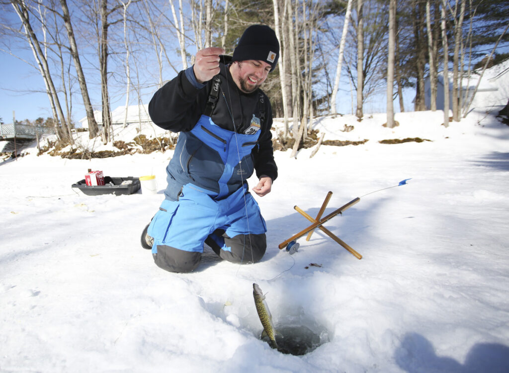 "Brian Rocray of Shapleigh pulls up a pickerel while fishing in a channel off Jordan Bay on Sunday in the Sebago Lake Rotary Ice Fishing Derby. ""We are keeping them to turn them in for the soup kitchen,"" he said. In past years, the Preble Street Soup Kitchen has turned the catch into enough chowder for 1,000 servings."