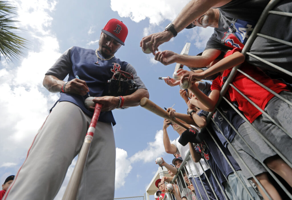 Center fielder Mookie Betts of the Boston Red Sox signs autographs for fans Monday during the team's first full-squad workout at spring training in Fort Myers, Fla.