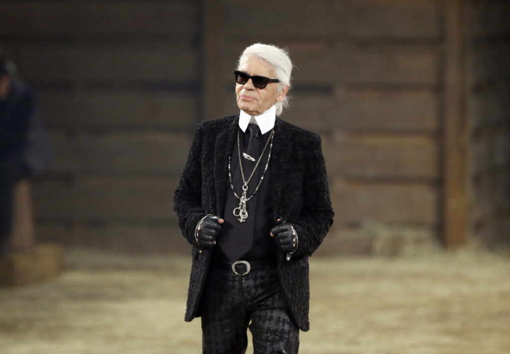 In this Tuesday 2013 file photo, Chanel designer Karl Lagerfeld takes a bow at the end of his Metiers d'Art fashion show in Dallas. Chanel's iconic couturier, Karl Lagerfeld, whose accomplished designs as well as trademark white ponytail, high starched collars and dark enigmatic glasses dominated high fashion for the last 50 years, has died. He was around 85 years old.