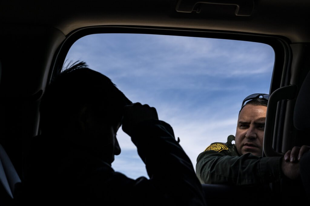 Border Patrol agent Daniel Hernandez speaks with a 14-year-old boy from Guatemala who was arrested after illegally crossing the U.S.-Mexico border alone in Organ Pipe Cactus National Monument National Monument in Ajo, Ariz.