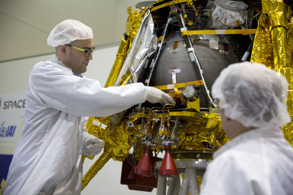 "SpaceIL co-founder Yonatan Winetraub, left, inserts a time capsule into a lunar module, an unmanned spacecraft, near Tel Aviv, Israel. A SpaceX Falcon 9 will launch Thursday night with Israel's ""immortal milestone"" lunar lander in tow."