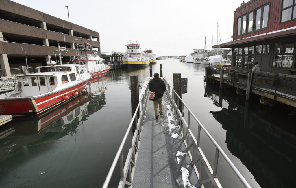 Rick Frantz, with Friends of Casco Bay, walks out on a dock between the Maine State Pier, left and Maine Wharf on Wednesday  to document an abnormally high tide.