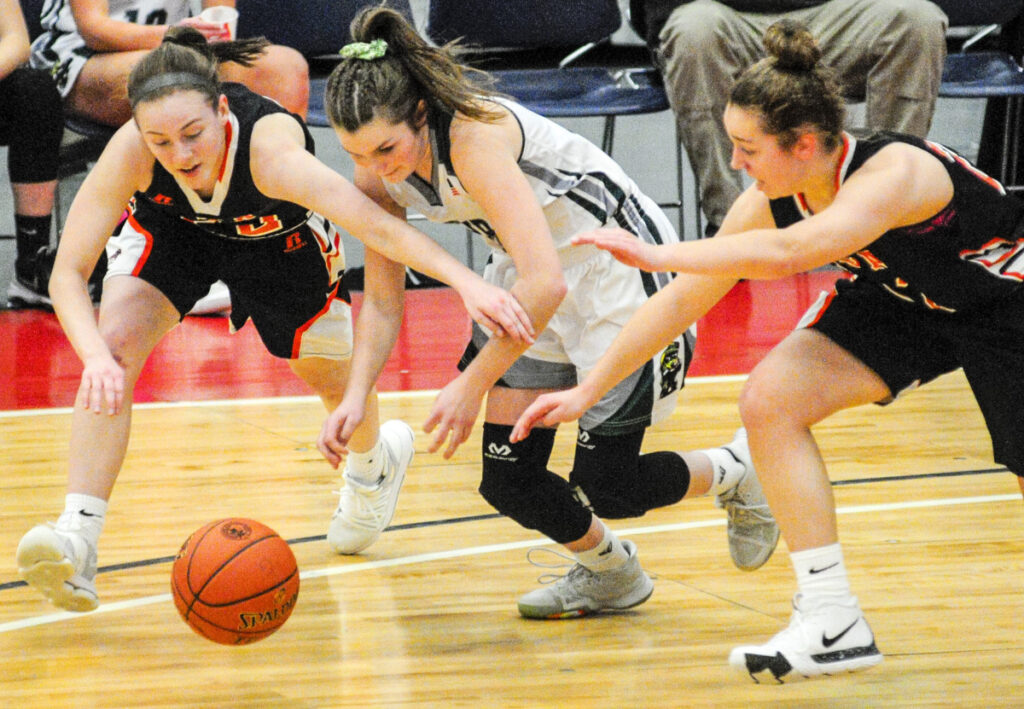 North Yarmouth Academy's Catherine Reid, left, and Serena Mower battle Winthrop's Maddie Perkins for a loose ball during their Class C South semifinal Thursday at the Augusta Civic Center. (Staff photo by Joe Phelan/Staff Photographer)