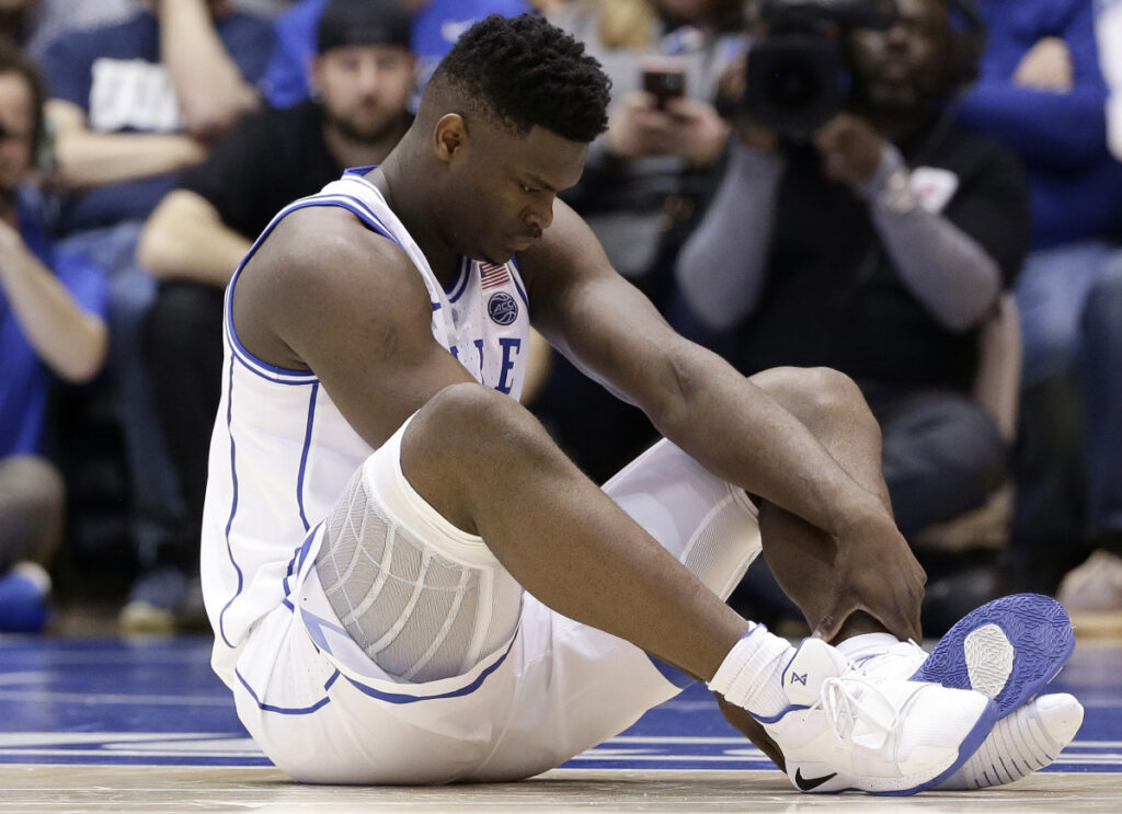 Duke's Zion Williamson, 18, sits on the court with his Nike sneakers, one ripped apart, after an injury during Wednesday's game against North Carolina.