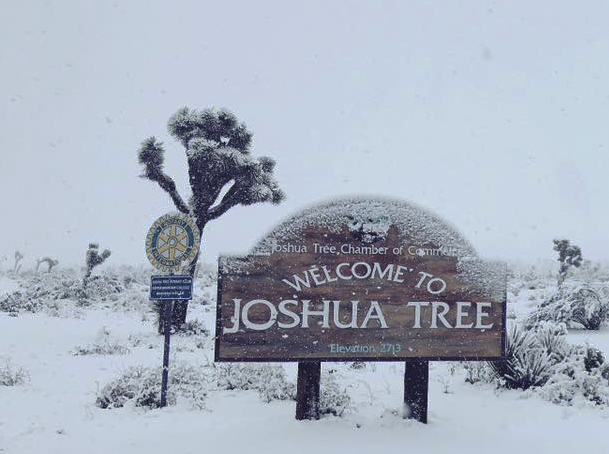 Snow sticks to the entrance sign to Joshua Tree National Park on Thursday. A cold weather system brought snow to extremely low elevations of Southern California and the San Joaquin Valley.