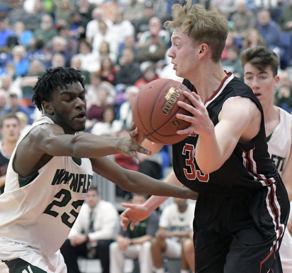 Tim Cookson of Hall-Dale attempts to keep the ball from Diraige Dahia of  Waynflete during Hall-Dale's 65-58 victory in a Class C South semifinal Thursday night as the Augusta Civic Center.