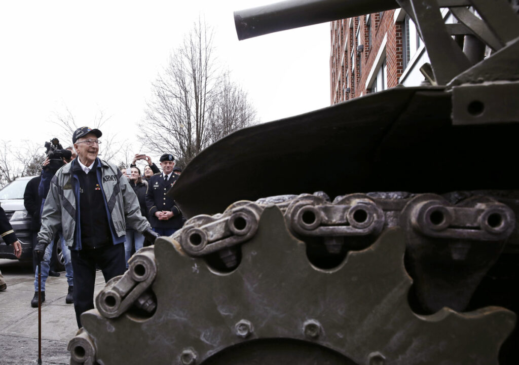 World War II tank gunner Clarence Smoyer admires a tank near the Charlestown Naval Shipyard in Boston, Wednesday.