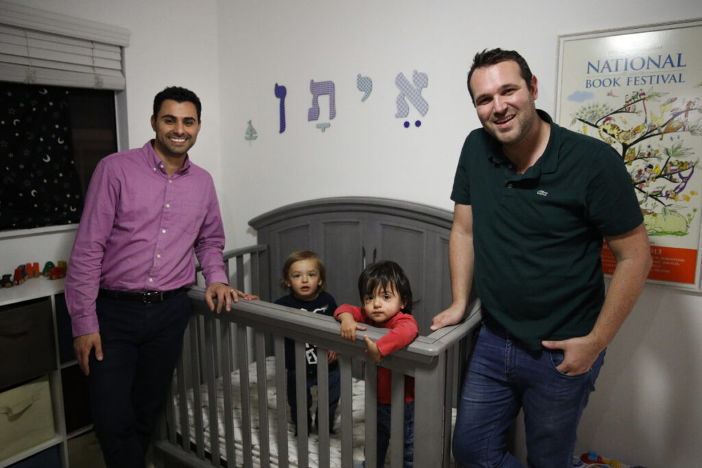 Elad Dvash-Banks, left, and his partner, Andrew, pose for photos with their twin sons, Ethan, center right, and Aiden in their apartment in Los Angeles in January.