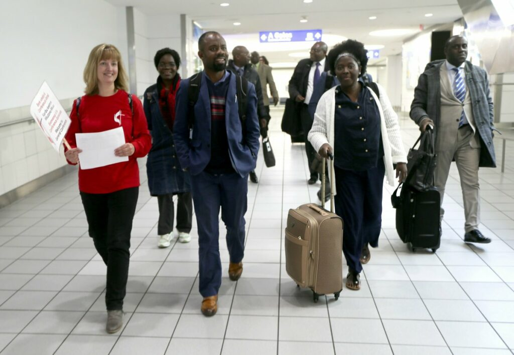 Methodist convention volunteer Kim Mertz of Chesterfield walks with The Rev. Quelende Andriano, center, and Rev. Dr. Elvira Cazombo, both of Angola, to the check-in table, as she welcomes delegates from African nations upon arrival Thursday, Feb. 21, 2019, at St. Louis Lambert International Airport. Andriano and Cazombo are among United Methodists in town to attend a special session to address homosexuality in the church. (Laurie Skrivan/St. Louis Post-Dispatch via AP)