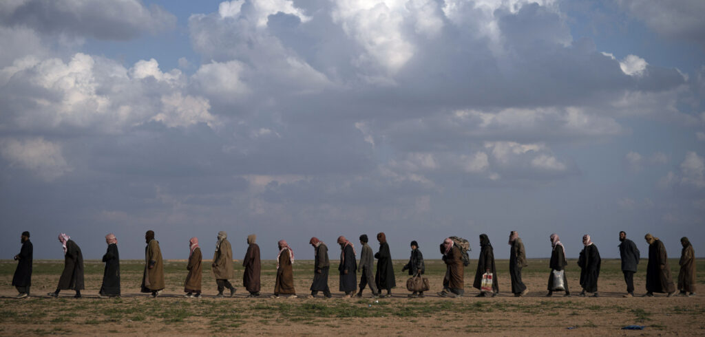 Men head for a screening site after being evacuated from Baghouz, eastern Syria, on Friday.