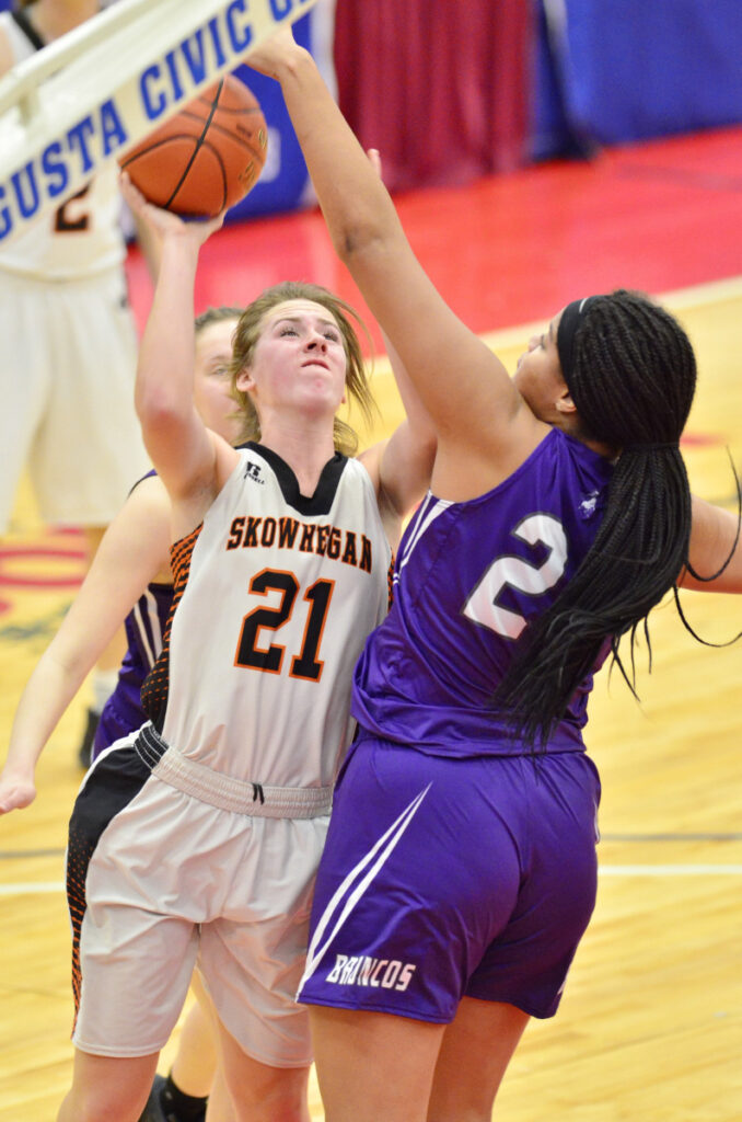 Hampden Academy's Bailey Donovan, right, blocks a shot by Annie Cooke of Skowhegan during the Class A North final Friday at the Augusta Civic Center. Hampden won, 32-28.