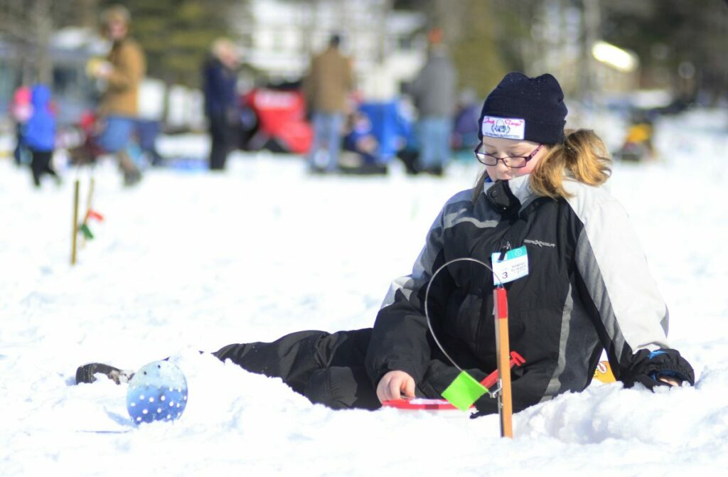 Danyka Blundon, 10, of Monmouth, sits on the ice while keeping a close eye on her trap during the Jack Traps children's ice fishing derby Saturday on Cochnewagon Lake in Monmouth.