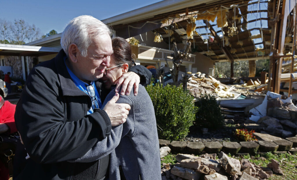 Pastor Steve Blaylock comforts his wife, Pat, amid the rubble that was once the First Pentecostal Church in Columbus, Miss., Sunday. A tornado Saturday wrecked havoc in the community, destroying a number of businesses and homes.