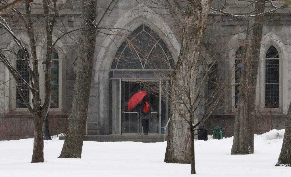 A unidentified student escapes the snow and rain as he ducks into Memorial Hall at Bowdoin College in Brunswick on Sunday. On Monday, Maine will see high winds followed by dropping temperatures.