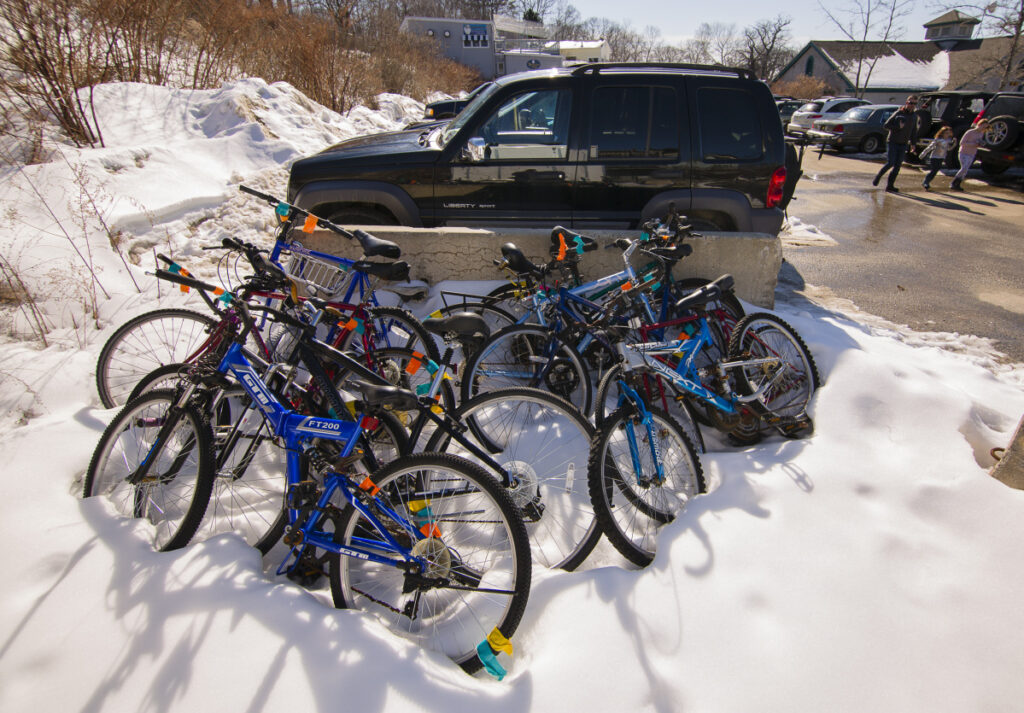 Apparently abandoned bicycles are stacked in the Peaks Island ferry parking lot Friday. Portland is gearing up to clamp down on abandoned bikes.