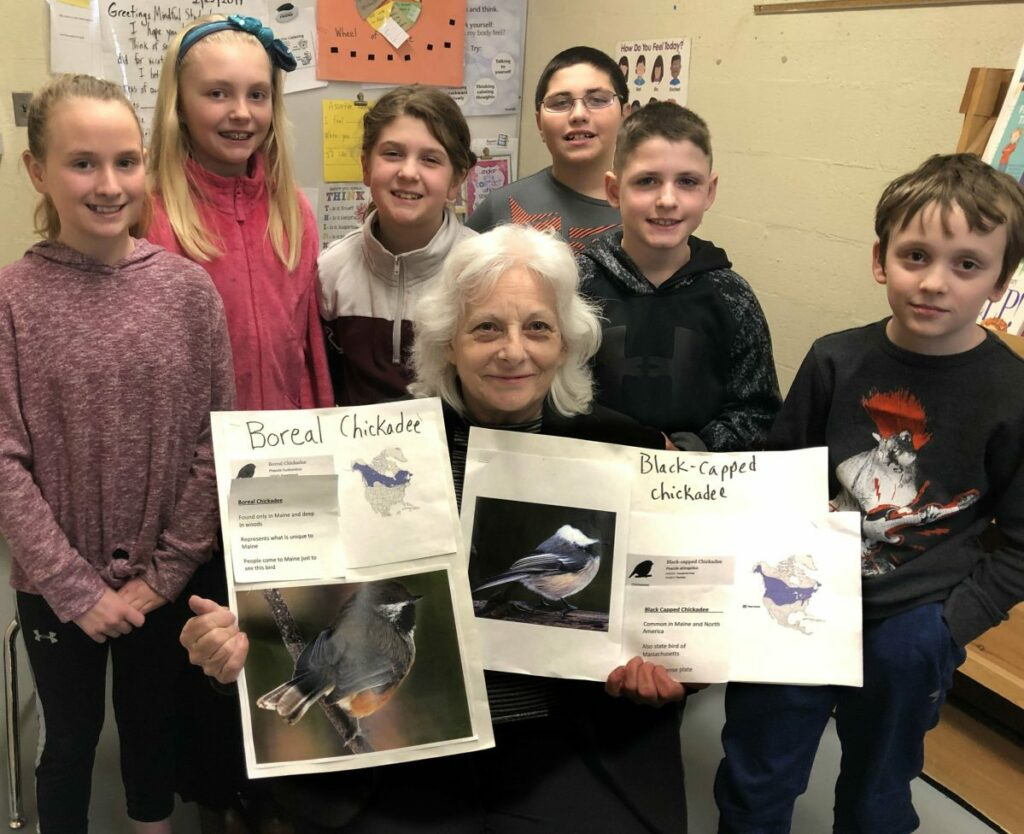 Surrounded by Margaret Chase Smith fourth-grade students, state Rep. Betty Austin of Skowhegan holds a picture of a boreal chickadee, on left, and a black-capped chickadee that may be chosen to be the officially designated Maine state bird after Austin submits the bill to a committee in Augusta this week. Students wrote letters that will accompany Austin.