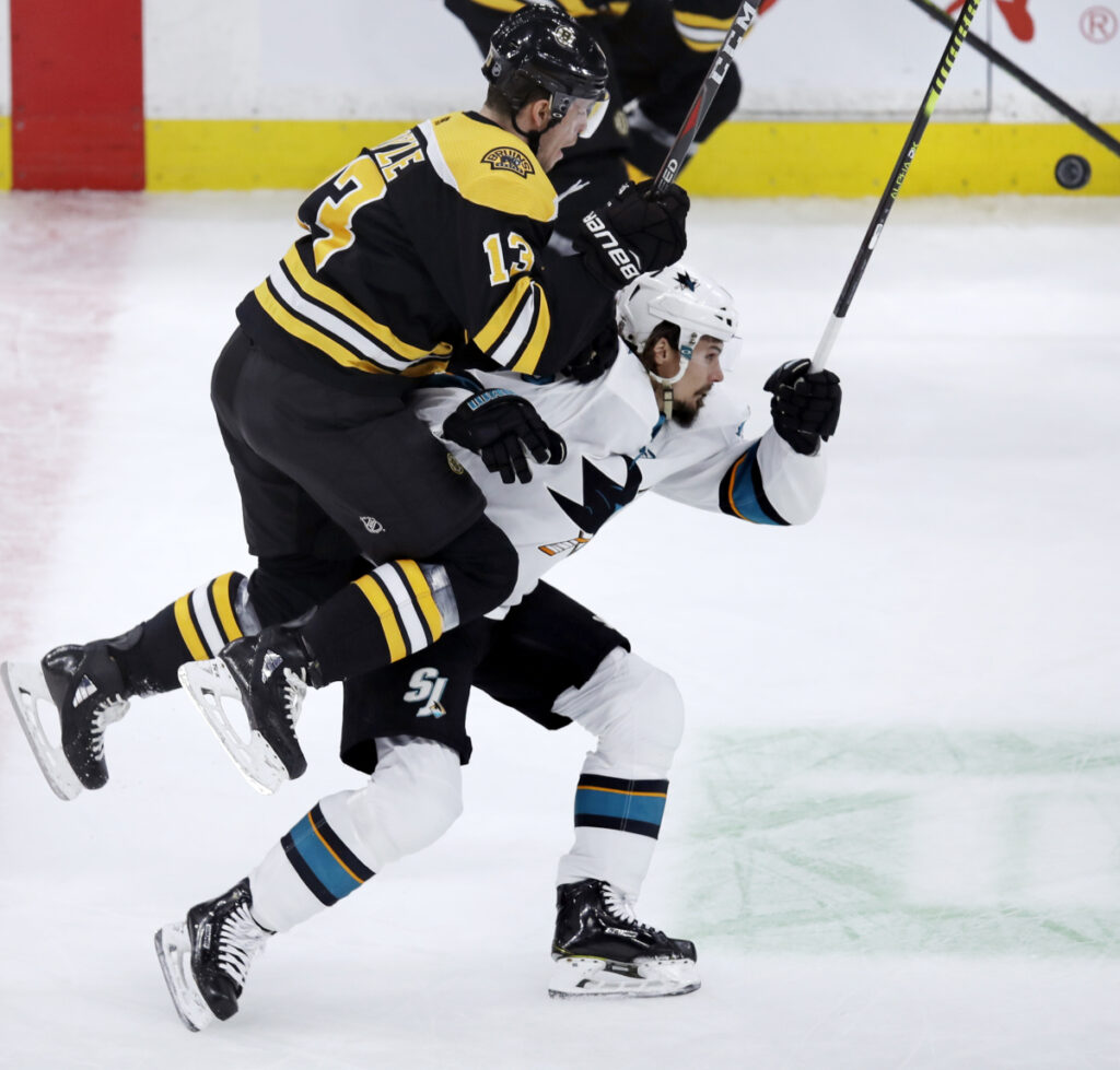 Charlie Coyle, playing his first home game for Boston, leaps onto the back of San Jose defenseman Erik Karlsson as they chase a puck in the first period Tuesday night. The Bruins won 4-1.