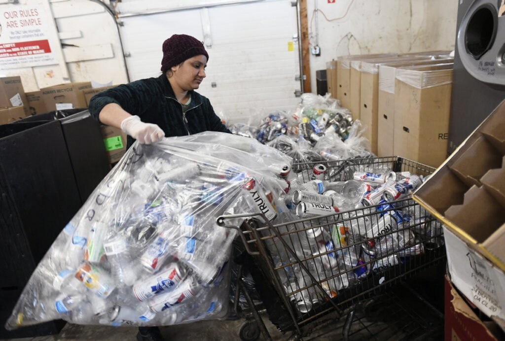 Pooja Paten, an employee of Madden Beverage and Redemption Center in Saco, empties a bag of returnables into a shopping cart to load into a reverse vending machine Wednesday.