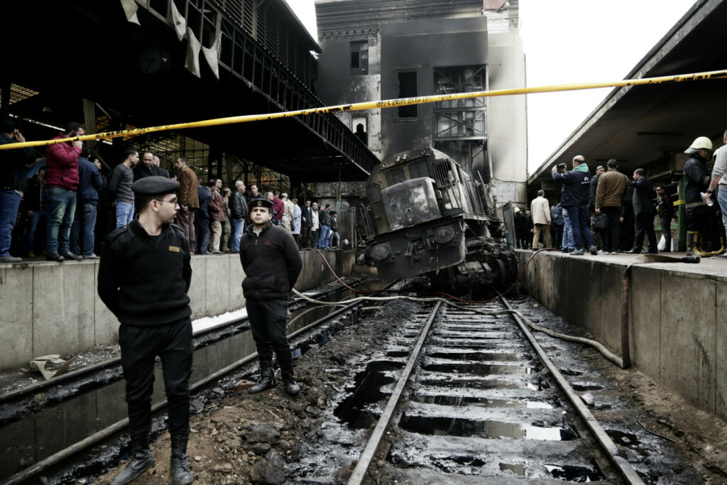 Police stand guard in front of a damaged train inside Ramsis train station in Cairo on Wednesday.
