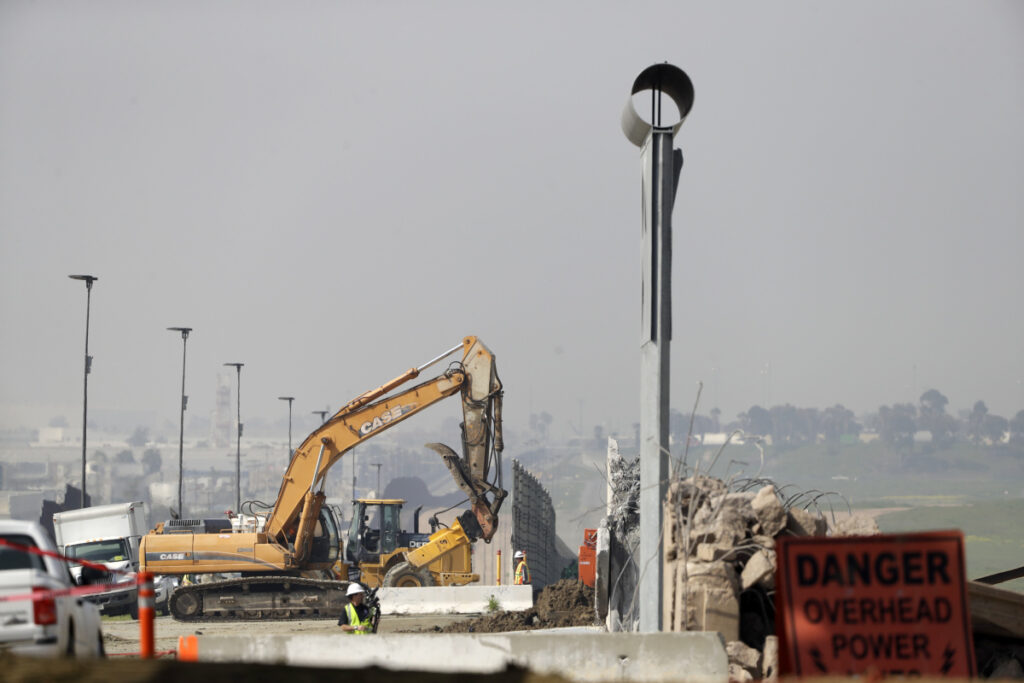 Crews work to demolish wall prototypes at the border between Tijuana, Mexico, and San Diego on Wednesday in San Diego.