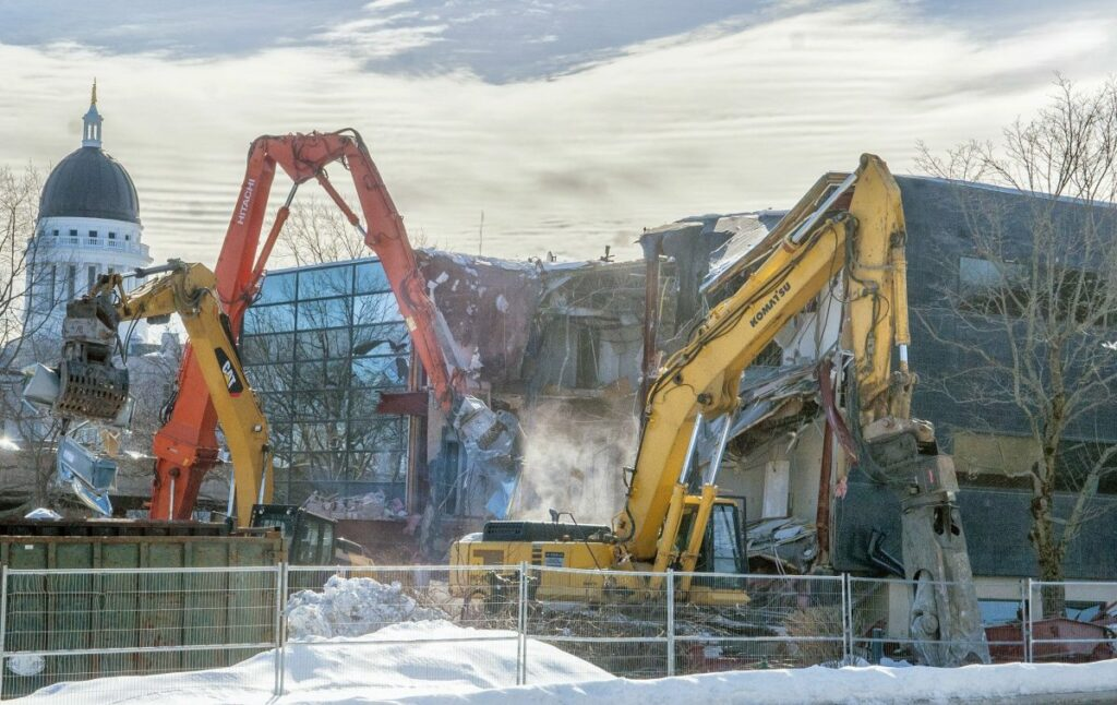 Excavators tear apart the old Maine Public Employees Retirement System building on Wednesday at the corner of Sewall and Capitol streets near the Maine State House in Augusta.