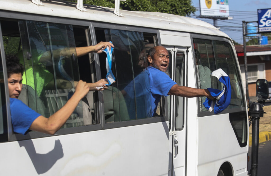 Alex Vanegas, right, and other prisoners who who had been imprisoned by the government of President Daniel Ortega for protesting against the regime, wave Nicaraguan flags aboard a prison bus, after being released, in Managua on Wednesday.