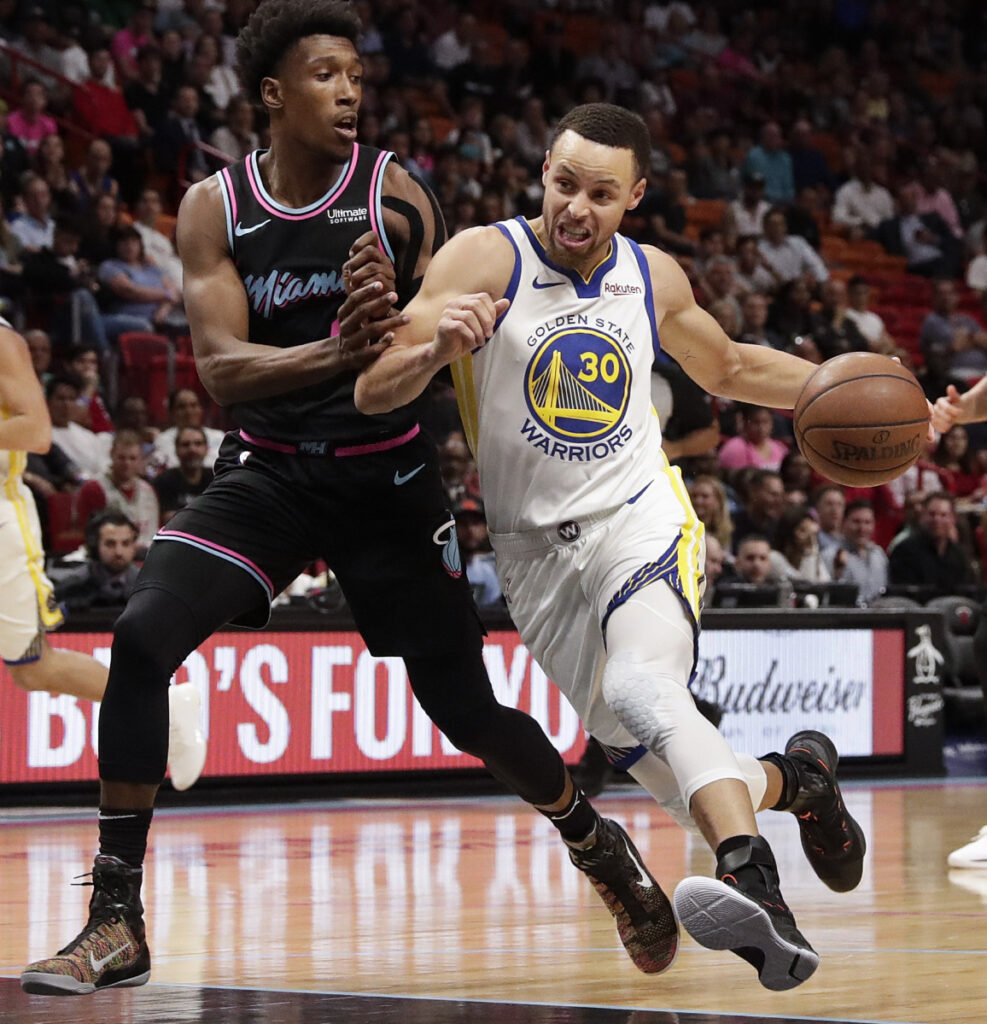Warriors Guard Stephen Curry Dribbles Toward The Basket Against Heat Josh Richardson In First