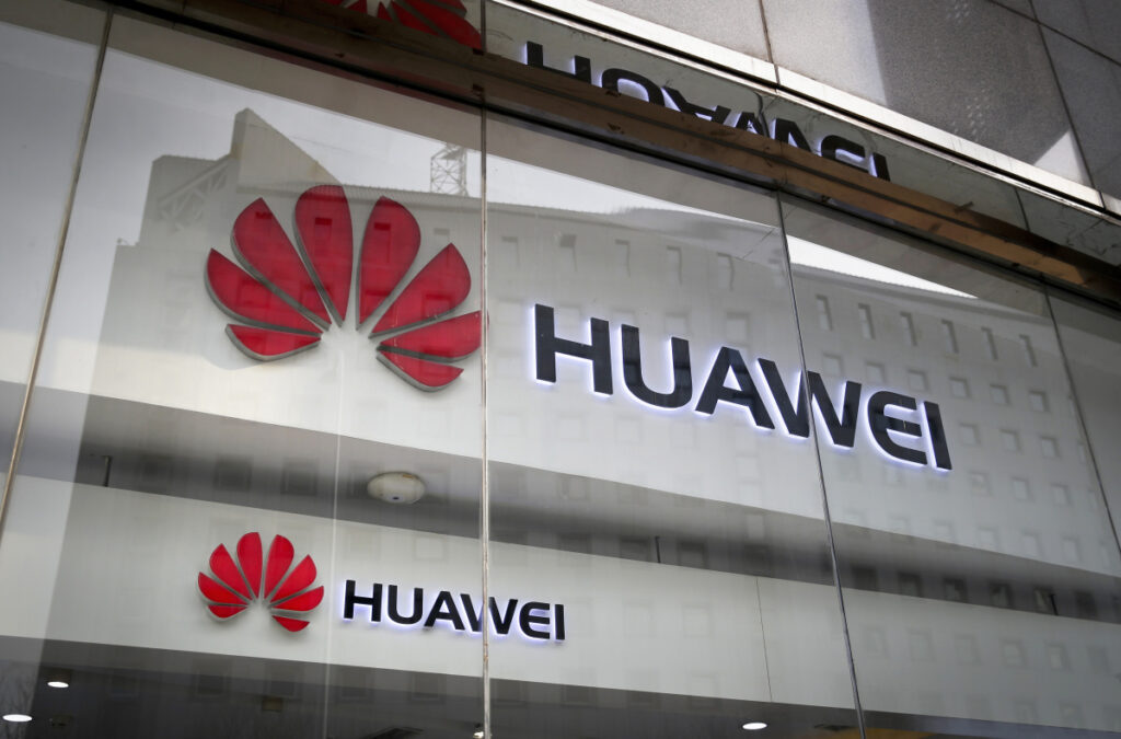 The logos of Huawei are displayed at its retail shop window reflecting the Ministry of Foreign Affairs office in Beijing.