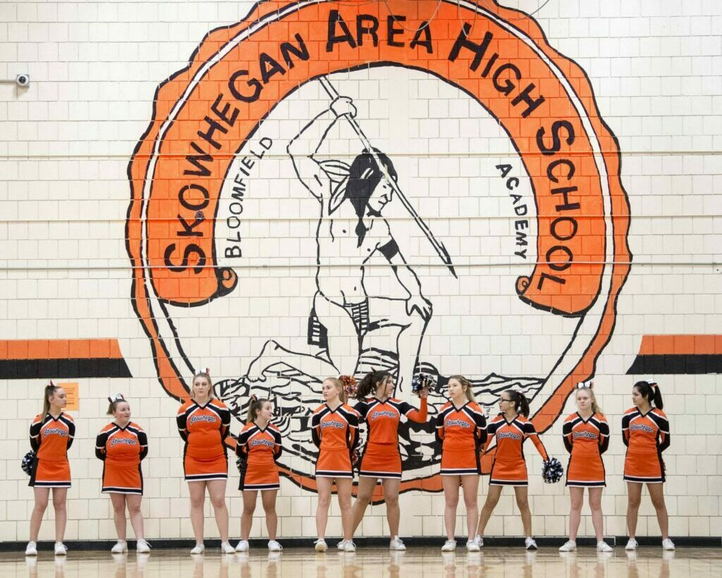 Skowhegan Area High School cheerleaders stand beneath the Indian mural on the wall of the gymnasium on Jan. 15, 2019.
