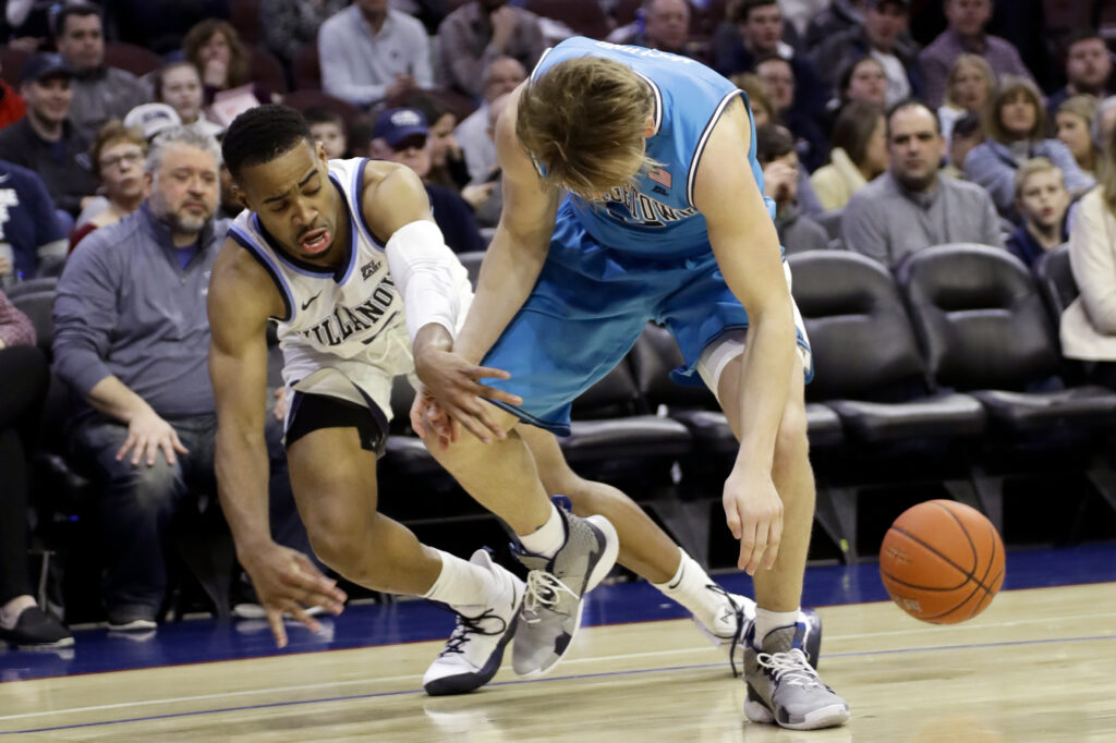 Villanova's Phil Booth, left, knocks the ball loose from Georgetown's Mac McClung during the Wildcats' 77-65 win Sunday in Philadelphia.