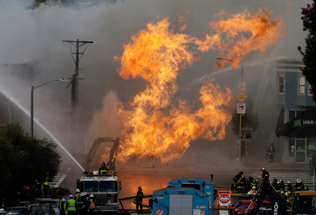 San Francisco firefighters battle a fire Wednesday that shot flames high into the air and burned several buildings as utility crews scrambled to shut off the flow of gas.