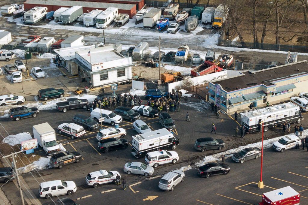 First responders and emergency vehicles gather near the scene of the shooting at an industrial park in Aurora, Ill., on Friday.