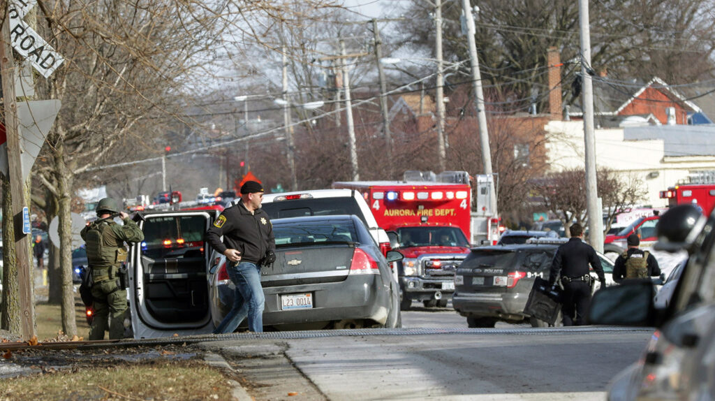 Law enforcement personnel gather near the scene of the shooting at an industrial park in Aurora, Ill., on Friday.