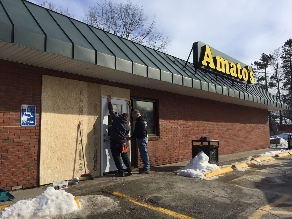 Mike Frongillo, left, and Aaron Bourassa of Great Falls Construction finish installing a temporary doorway Saturday after a customer crashed into the glass entryway of Amato's at 1108 Broadway in South Portland. The morning crash closed the pizza-and-sandwich shop for the day, but it will be open as usual Sunday from 7 a.m. to 11 p.m.