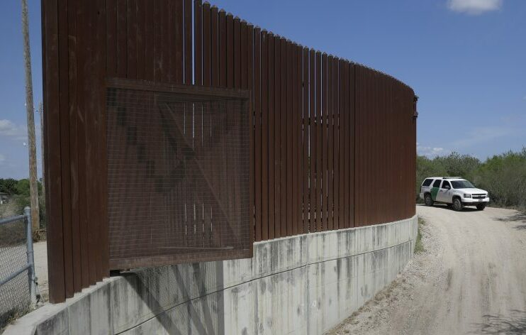 A U.S. Customs and Border Patrol vehicle passes along a section of border levee wall in Hidalgo, Texas on Aug. 11, 2017.