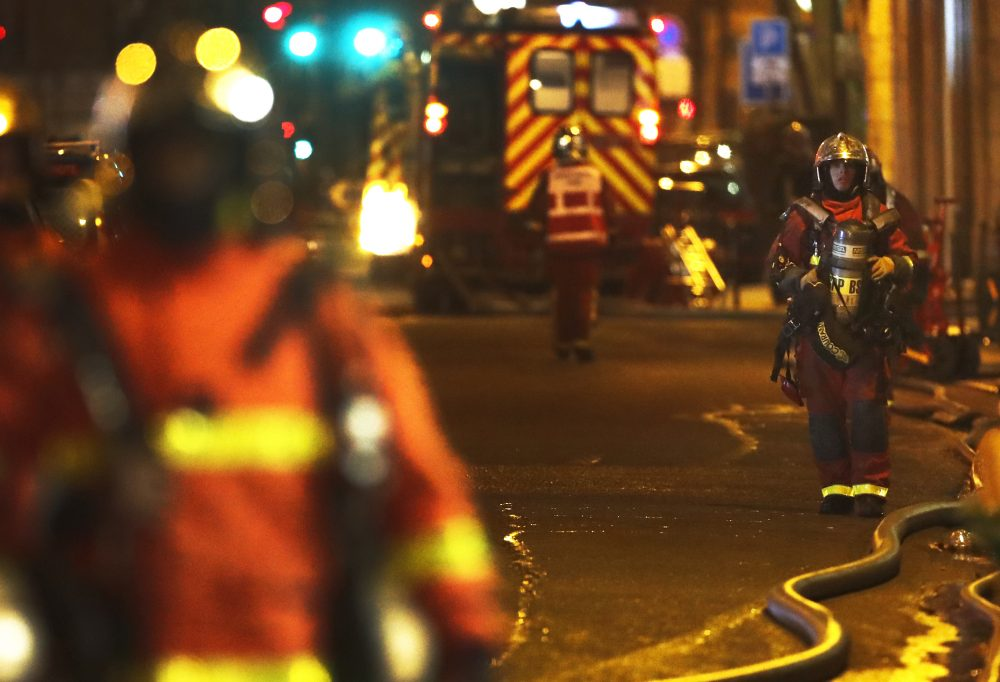 Firefighters stand on the scene of a fire in Paris, Tuesday, Feb. 5, 2019. A fire in a Paris apartment building early Tuesday killed seven people and sent residents fleeing to the roof or climbing out their windows to escape, authorities said. (AP Photo/Christophe Ena)