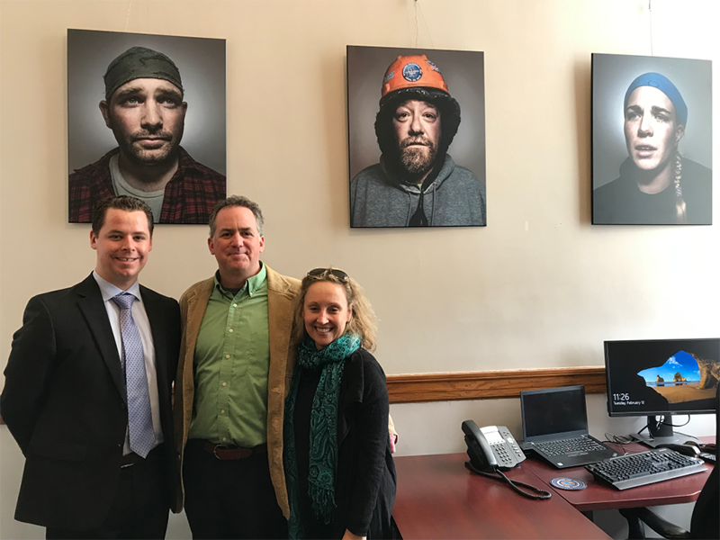 The Senate president's Chief of Staff BJ McCollister, Hopper McDonough and Heather Perry pose in front of shipbuilder portraits hanging at the state house.