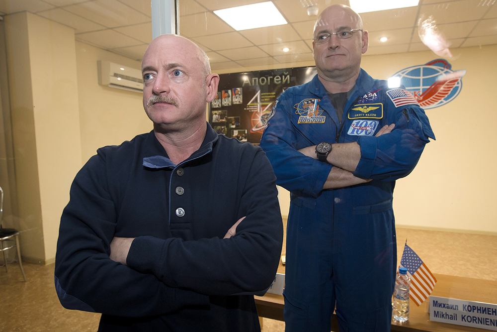 Scott Kelly, right, crew member of the mission to the International Space Station, stands behind glass in a quarantine room, behind his brother, Mark Kelly, also an astronaut in 2015.