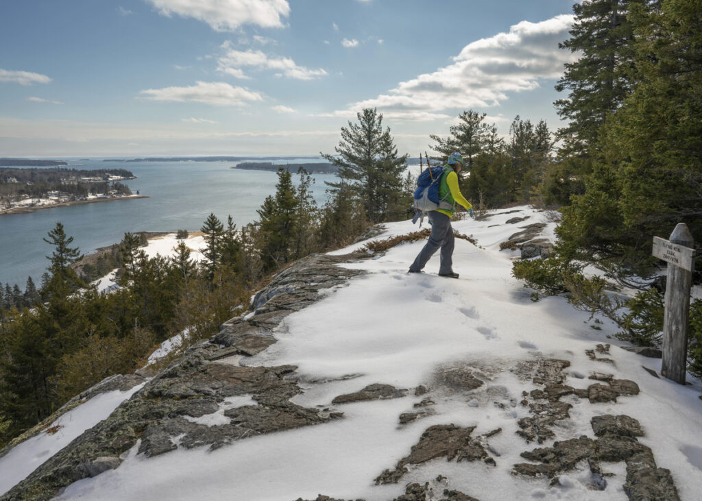 Jayme Rec leaves the summit of Flying Mountain in Acadia National Park. The trail up to the summit of Flying Mountain above Somes Sound was untracked and required some careful route finding with some of the trail blazes on rocks covered by snow. Parts of the trail were completely covered in ice and required traction aid footwear like the Yaxtrax.