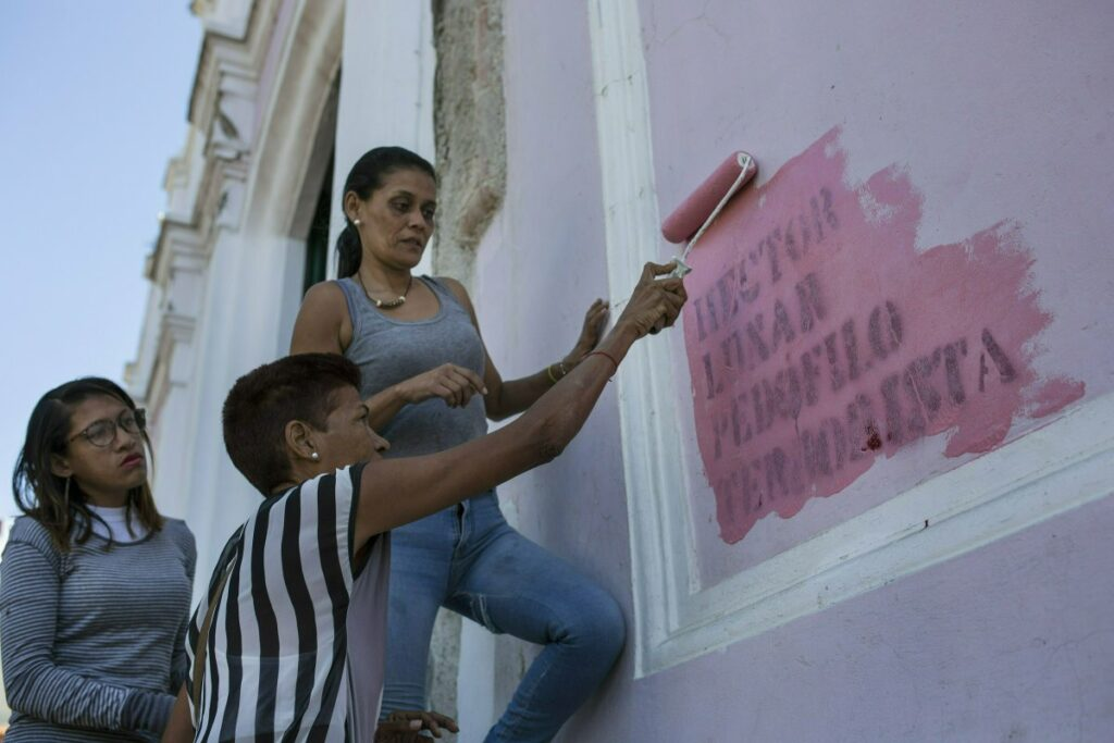 """Faithful paint over graffiti that reads in Spanish: """"HECTOR LUNAR, PEDOPHILE, TERRORIST,"""" on a wall of the Dulce Nombre de Jesus church, in the Petare slum of Caracas, Venezuela. While appalled by the slurs, Monsignor Hector Lunar says he feels no need to defend himself. Parishioners show their support, he says, by filling the pews, knowing the attacks tapping into the worldwide sex-abuse scandals rocking the Roman Catholic Church come from Nicolas Maduro loyalists intent on discrediting him."""