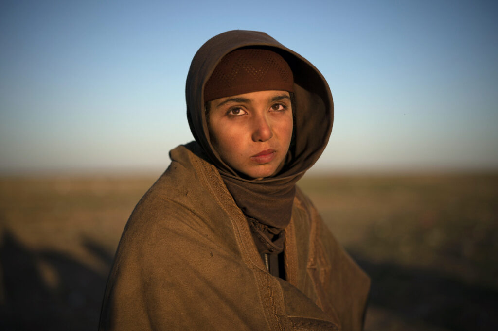 A girl waits to be screened by U.S.-backed Syrian Democratic Forces after being evacuated out of the last territory held by Islamic State militants in the desert outside Baghouz, Syria, on Friday.