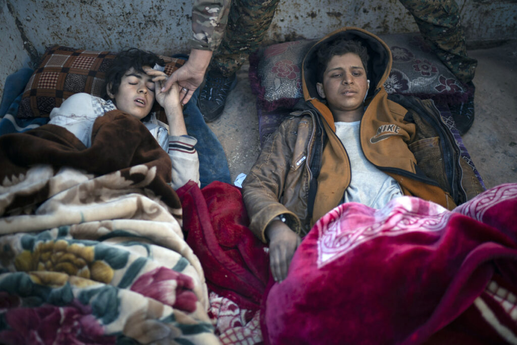 Two injured boys suspected of being Islamic State supporters lie on the back of a truck at a U.S.-backed Syrian Democratic Forces screening area after being evacuated out of the last territory held by Islamic State militants in the desert outside Baghouz, Syria, on Friday.
