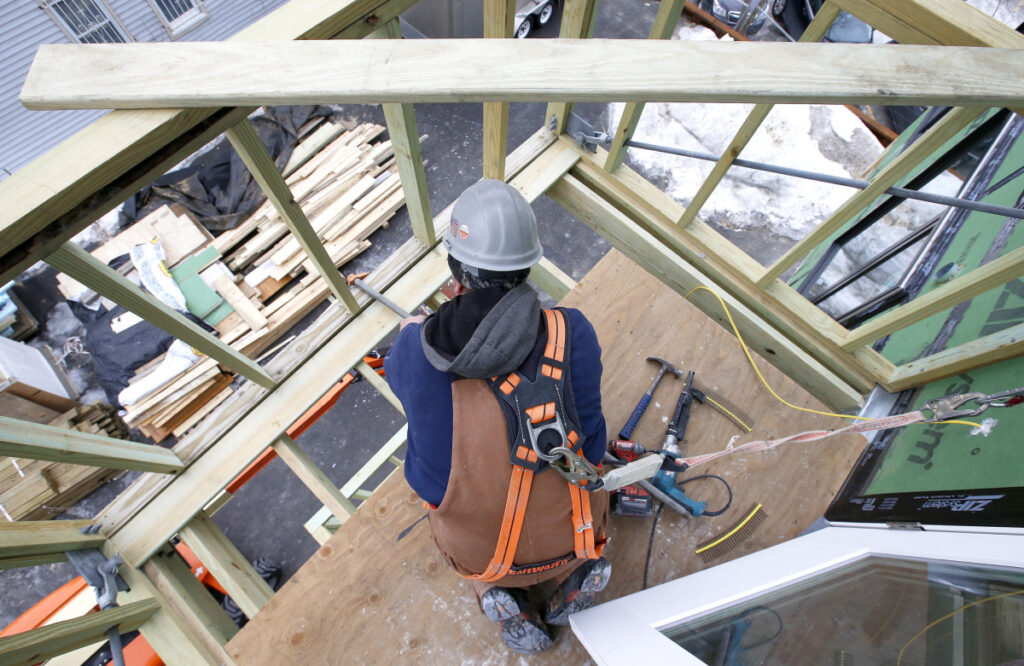 Carpenter Jay Nilsson lays decking on a balcony at Parris Terrace, a mid-range condominium project under construction in Portland's Bayside. Construction costs have risen to their highest point since the Great Recession.