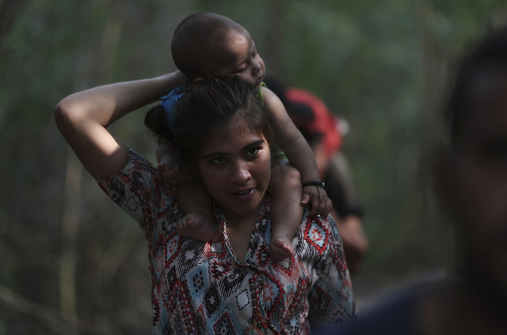 A woman flees with her baby Sunday into Colombia from Venezuela, where a standoff continues between Venezuelan President Nicolas Maduro and opposition leader Juan Guaido. Guaido has declared himself president, claiming that Maduro's recent re-election was illegal. The United States and about 50 other countries recognize Guaido's claim.